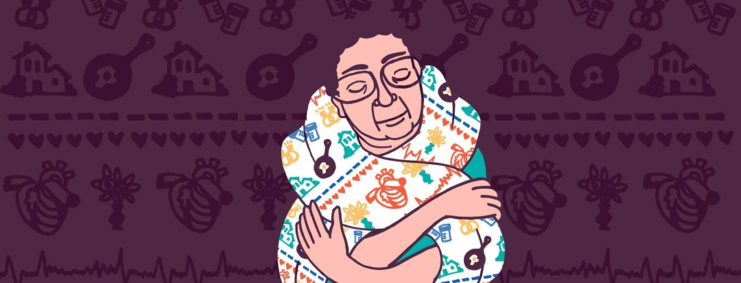 a woman is wrapped in a scarf with a pattern of homes and hearts on it