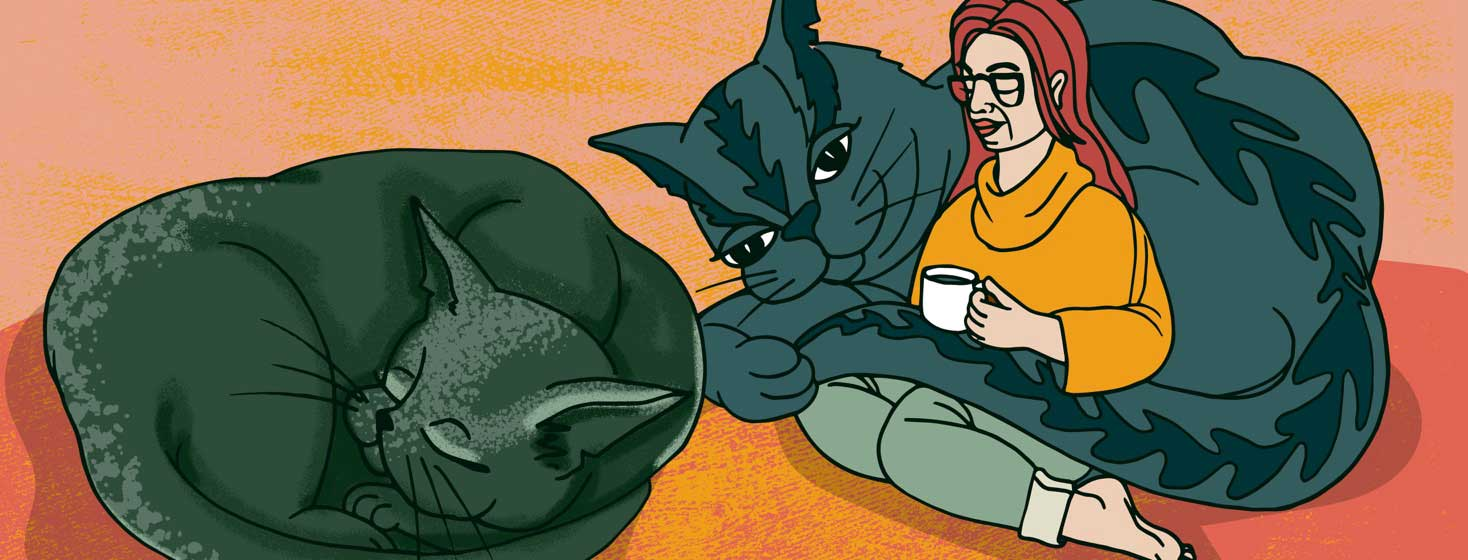 a woman sips tea with her two enormous cats