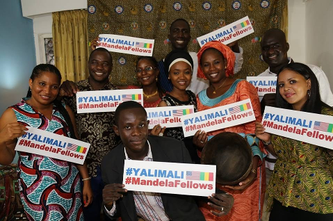 Smiling men and women holding up signs with the hastag YaliMali.