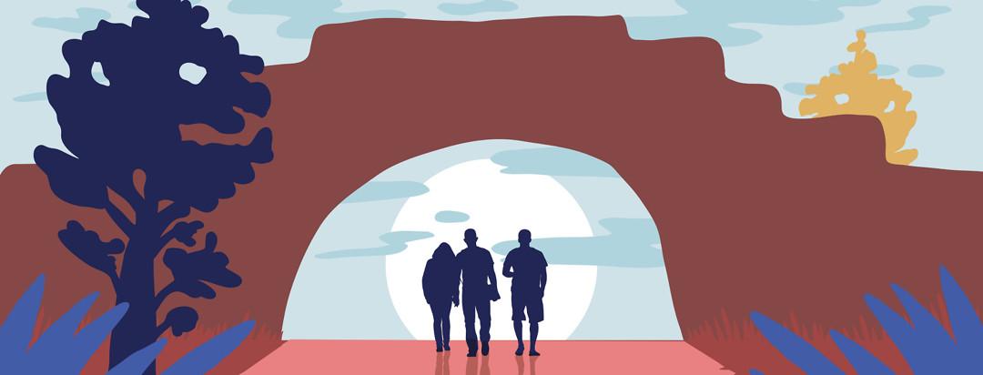 three friends walk through a natural stone arch