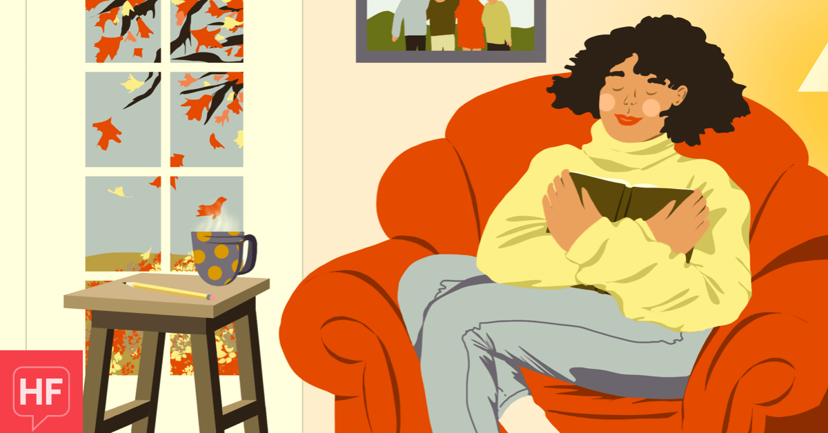 A woman sits in a comfy chair near a window where autumn leaves are falling. She has an open journal pressed to her chest and is smiling with her eyes closed. fall cozy gratitude grateful thankful female adult POC