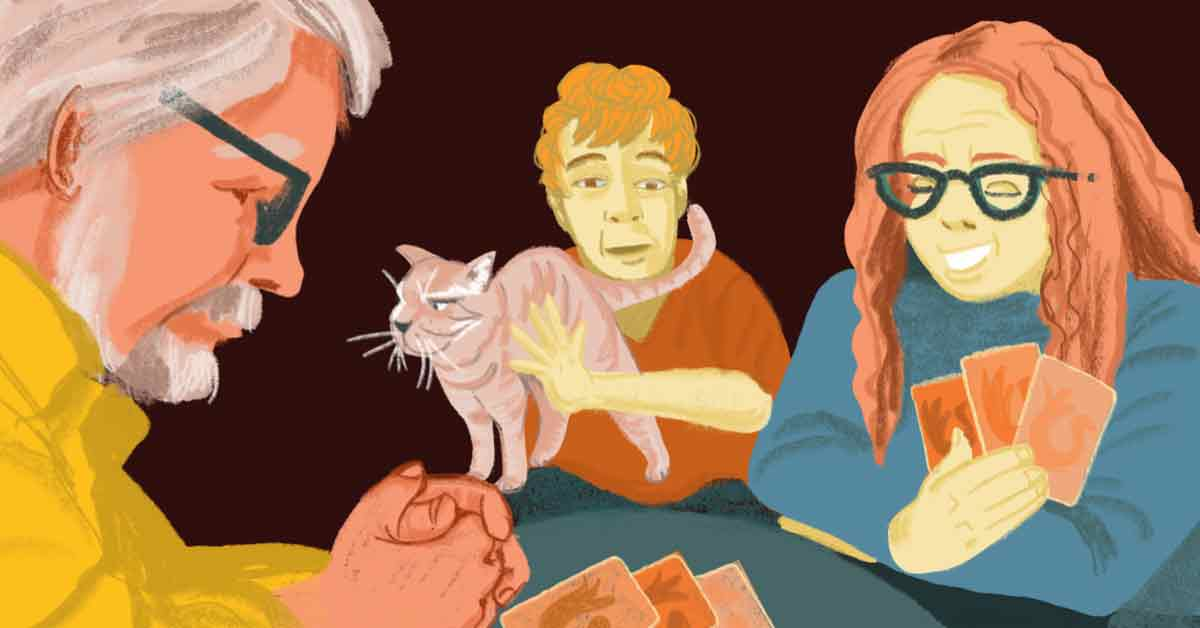 A family playing a card game together with a cat on a man's lap